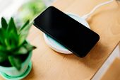 Smartphone In Mint Silicone Case Is Charged From A Wireless Charger. The Mobile Phone Is Charged On  poster