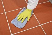 foto of grout  - Worker With Yellow Gloves And Blue Towel Clean Red Tiles Grout - JPG