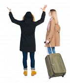 Back view of two woman in winter jacket traveling with suitcas. Back view. Rear view people collecti poster