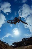 Biker Jumping Against Sun