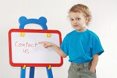Schattige lachende jongetje toont het woord contact ons op een whiteboard