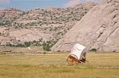stock photo of trailblazer  - A white and brown covered handcart in a field in Wyoming - JPG