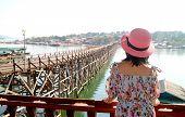 Woman In Pink Hat Admiring The Mon Bridge, Stunning Landmark Of Sangkhlaburi District, Thailand poster