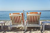 Sun Loungers With Orange Mattresses On A Sandy Beach On The Background Of A Calm Blue Sea. Idyll And poster