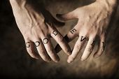 Man with Good and Evil (fake) tattoos on his hands.