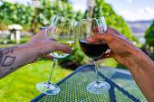 Man And Woman Hands Cheering Wine Glasses As They Sitting Against Beautiful Landscape Of Winery Vine poster