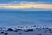 The sea after sundown and pebble beach at dawn -- Twilight seascape with water blurred by motion poster