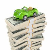 Small green car on a big pack of dollars.