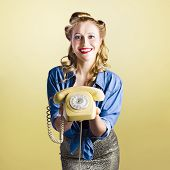 stock photo of olden days  - Adorable female pinup model holding olden day rotary phone in a call us now concept on yellow gradient background - JPG