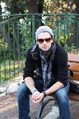 Young Stylish Man Sitting On A Bench