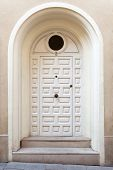 Receded White Wooden Door With Arched Frame And Two Steps