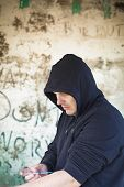 Drug addict man with syringe in hands on a wall background