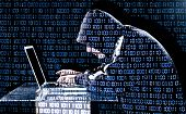 stock photo of theft  - Hacker typing on a laptop with binary code in background - JPG