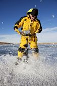 picture of auger  - Ice flies everywhere as an ice fisherman uses an auger to make his fishing hole - JPG