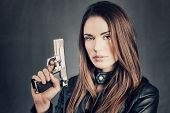 image of gunshot  - beautiful woman holding up her gun in studio - JPG