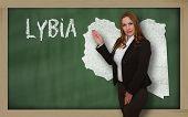 Teacher Showing Map Of Lybia On Blackboard