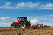 foto of farm landscape  - Farmer plowing the field. Cultivating tractor in the field. Red farm tractor with a plow in a farm field. Tractor and Plow