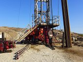 stock photo of roustabouts  - An oil well servicing rig with stacked pipe is set up in Kern County - JPG
