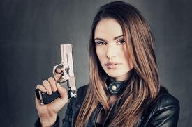 pic of gunshot  - beautiful woman holding up her gun in studio - JPG
