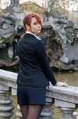 Elegant Red-head Girl Outdoors Against Stone Banister