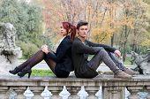 Elegant Couple Sitting Back To Back On Stone Balusters
