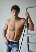 Young muscular man leaning on a stepladder