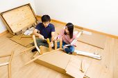 Furniture assembling by asian couple