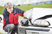 Adult upset driver man inspecting automobile body after crash car collision accident