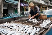 MACAU - OCTOBER 30: Fisherman prepares fish for drying on the grid in the fishing port on October 30