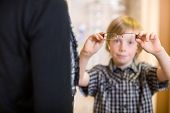 Preadolescent boy holding spectacles with mother in foreground at shop