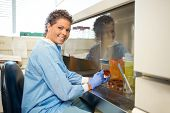 picture of fumes  - Side view portrait happy female researcher with petridish working in laboratory - JPG