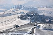 Narrow road through hills and vineyards covered with snow towards small village in Piedmont, Northern Italy.