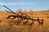 stock photo of plow  - An old rusty  three bottom plow is left abandoned in tall prairie grass - JPG