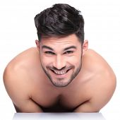 shy young naked man smiling to the camera on white background