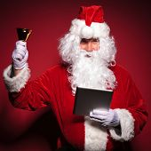 santa claus is ringing his bell while reading news on his tablet pad, on red background