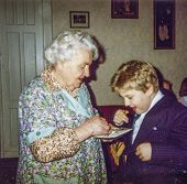 Vintage photo of great-grandmother and great-grandson blessing each other and sharing Christmas wafe