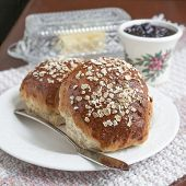 A healthy variety of whole grain breads, oatmeal molasses bread. On a plate with jam and butter.