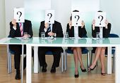 stock photo of query  - Row of businesspeople with question marks signs in front of their faces - JPG