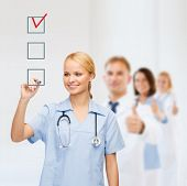 healthcare, medical and technology - smiling doctor or nurse drawing red checmark into checkbox