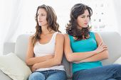 stock photo of not talking  - Unhappy young female friends not talking after argument at home on the couch - JPG