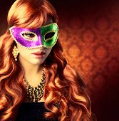 Masquerade. Beautiful Girl in a Carnival mask. Beauty Glamorous Woman Celebrating. Holiday Make up and Hairstyle. Long Red Wavy Hair