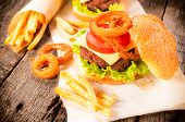 foto of fried onion  - Onion ringsbeef burger and french fries on the table - JPG