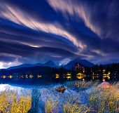 Milky Way over the lake in National Park High Tatra. Dramatic overcast sky. Strbske pleso, Slovakia,