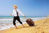 Full length portrait of a lost businessman carrying a suitcase at sandy beach