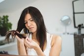 picture of split ends  - Woman checking the ends of her long brunette hair for condition and split ends with a grimace on her face as she stands in the bathroom - JPG