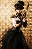 Portrait of a beautiful steampunk woman holding a gun over vintage background.