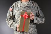 Closeup of a soldier holding a Christmas present. The gift is wrapped in gold paper with red ribbon and bow. Horizontal format. Man is unrecognizable.