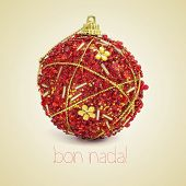 a red and golden christmas bauble and the text bon nadal, merry christmas written in catalan, on a b