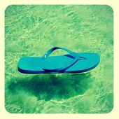 picture of a blue flip-flop on the seawater in the summer, with a retro effect