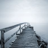 Old Ruined Wooden Pier Perspective On The Lake In Foggy Morning